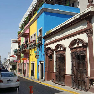 Buildings painted in green, pink, yellow and blue on a street.