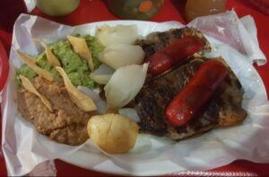Carne asada with Mexican sausage, refried beans, guacamole, grilled onion, chips and potato.