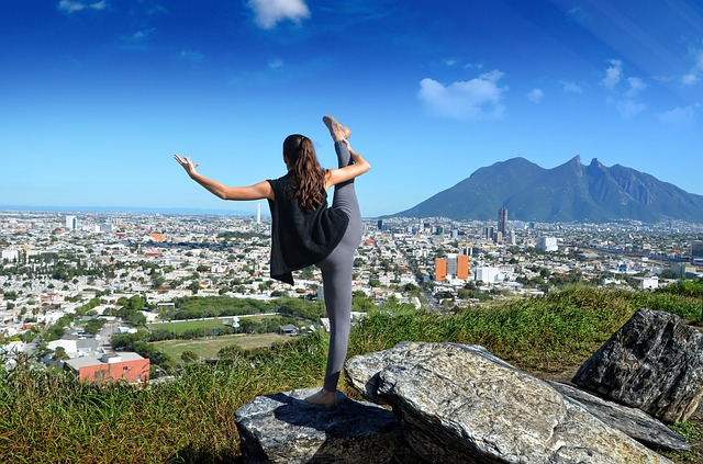 Young woman stretching her leg and watching a hill at the distance.