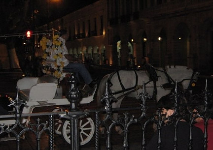 Horse-drawn carriage at night.
