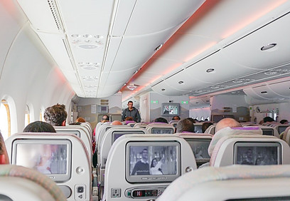 Several passengers watching shows on the airplane's screens.