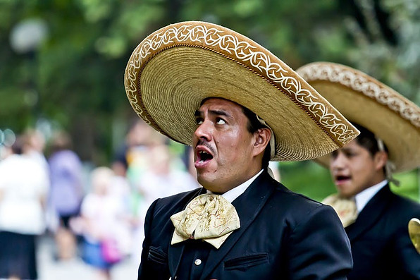 Mexican man singing dressed in mariachi attire.