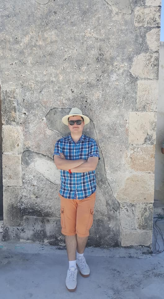 Young man wearing a plaid shirt, orange shorts, white sneakers, and a straw hat leaning against the wall.
