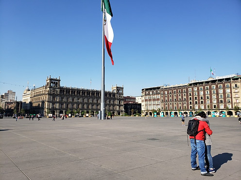 Zocalo in Mexico City with colonial buildings in the back and a giant Mexican flag in the middle.