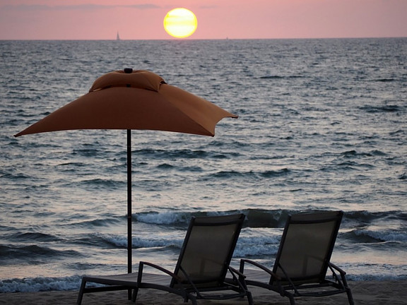 Two chairs and an umbrella with the sunset as backdrop.