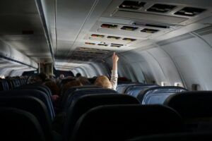 Passengers inside an airplane with one of them raising his hand.