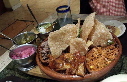 Plate with pork rinds, carnitas, shredded pork meat, guacamole, red onion and chili peppers.