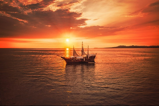 Boat in the middle of the sea with the sunset as backdrop.