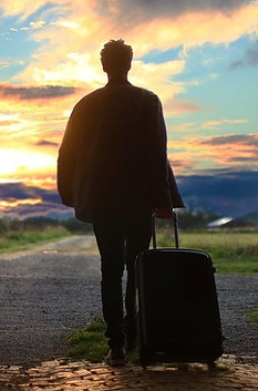 Man waking against the sun rolling his suitcase.