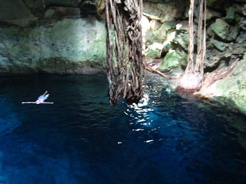 Man floating inside a cenote in Yucatan.