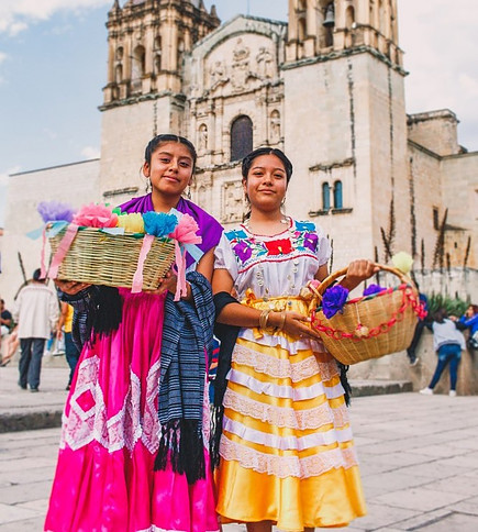 Two indigenous women wearing traditional clothes and carrying two baskets outside the Oaxaca Cathedral.