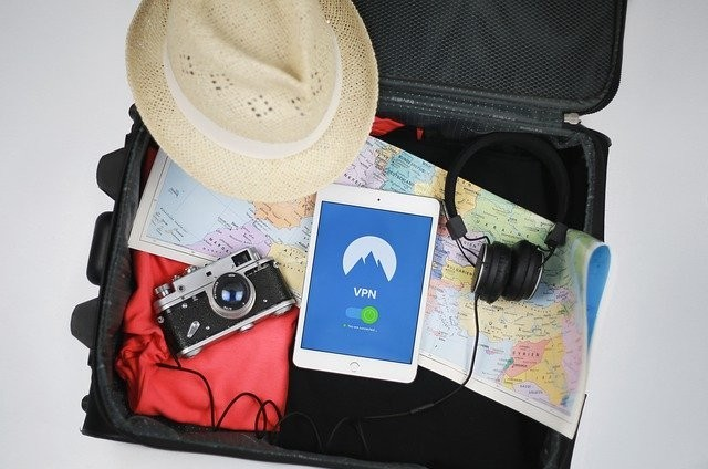 Open suitcase with clothes, a hat, a tablet, a map and a camera.
