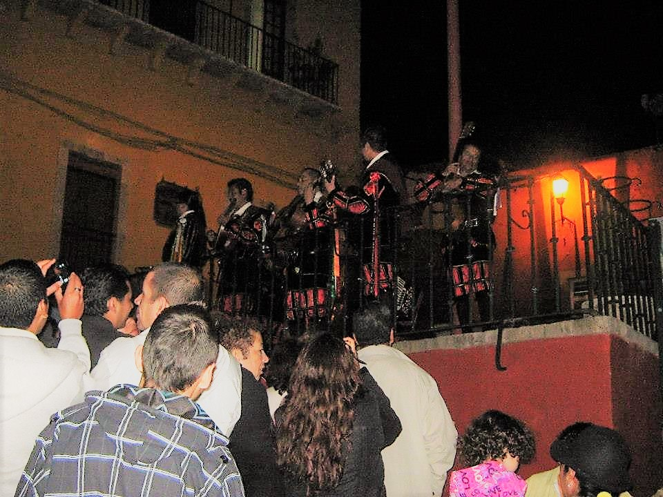 A crowd listening to an old Spanish music band in Guanajuato at night.