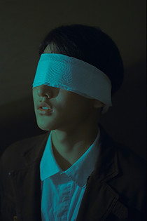Man with a white blindfold.