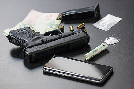 Black firearm, cellphone, drugs and money.
