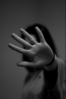 Foregroung photo of a woman's palm blocking her face.