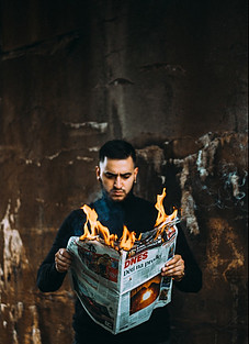 Man reading a burning newspaper.