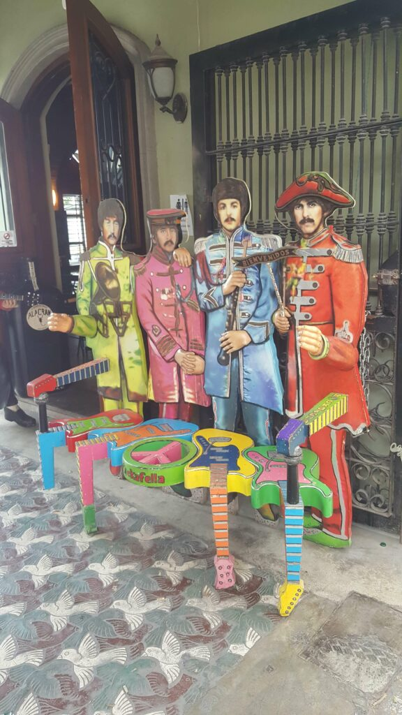 Colorful bench made of guitars and the Beatles in the back.