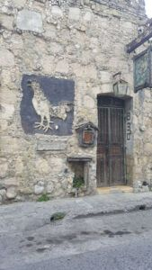 Old stone building with a rooster sign at the entrance.