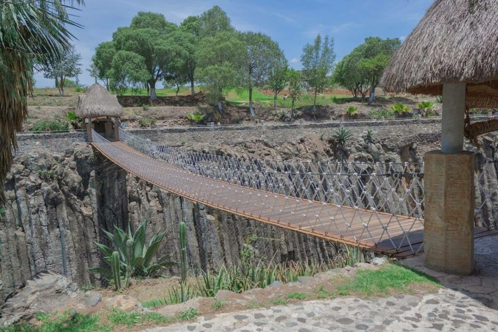 Basalt formations with a suspended bridge in the middle.