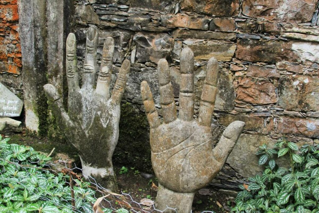 Two sculptures shaped like hands surrounded by plants and a stone wall in the back.