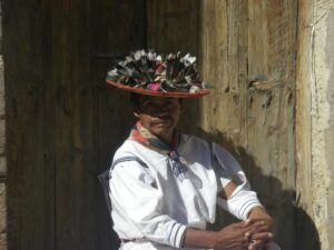 Man seated and wearing traditional Huichol clothing.