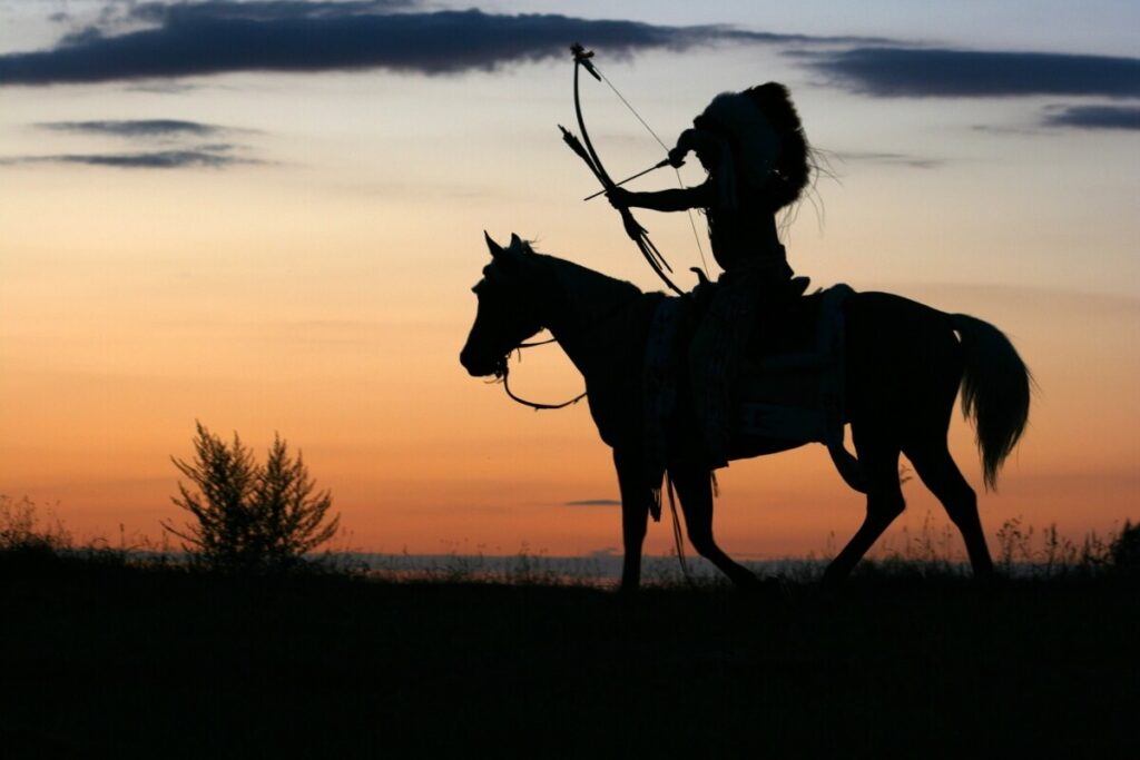 Apache riding a horse and holding a bow in his hand.