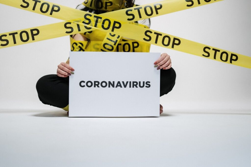 Woman holding a coronavirus sign surrounded by yellow tape reading stop
