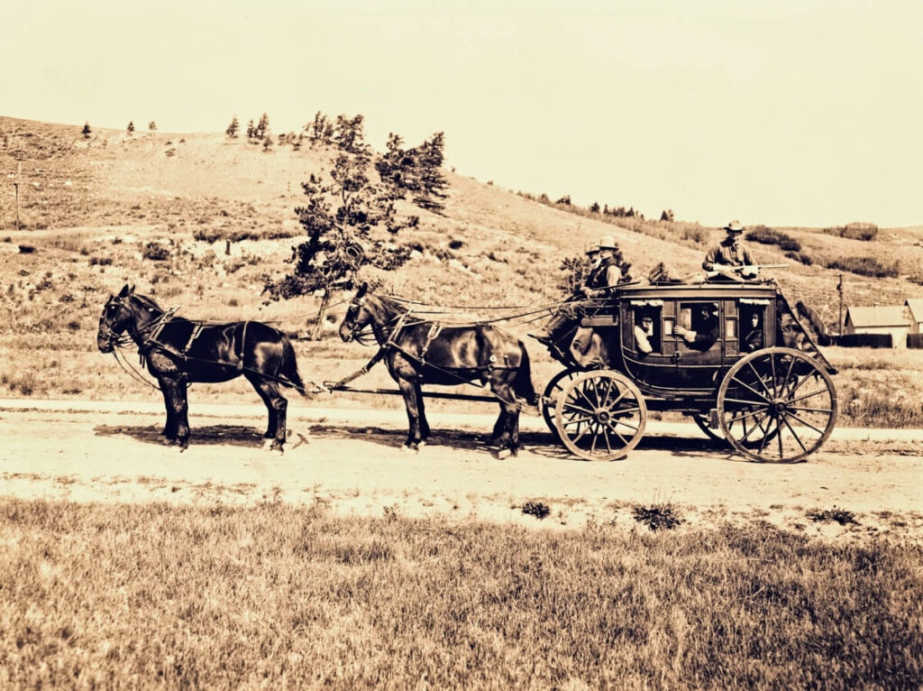 Men escorting a stagecoach.