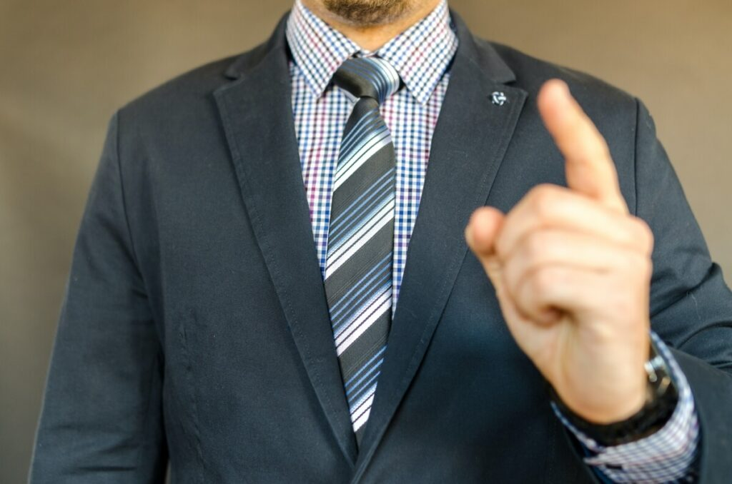Man in suit pointing with his left hand.