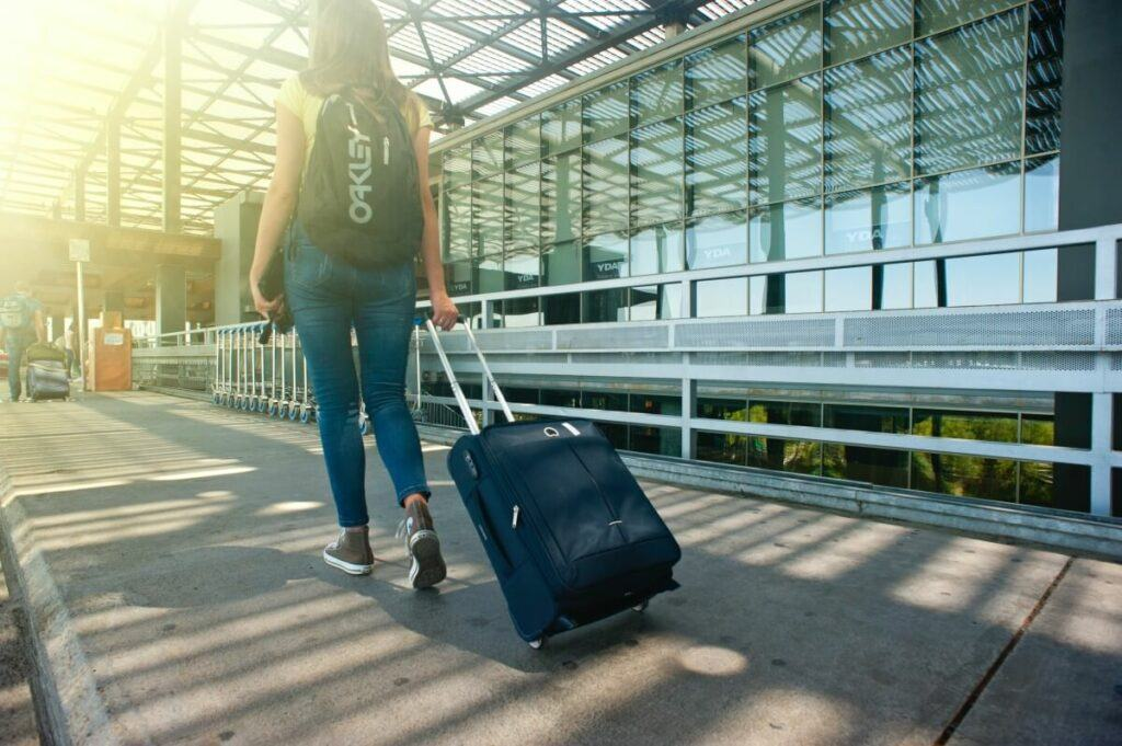 Young woman dragging a suitcase at the airport.