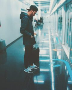 Young man waiting at the airport with his suitcase.