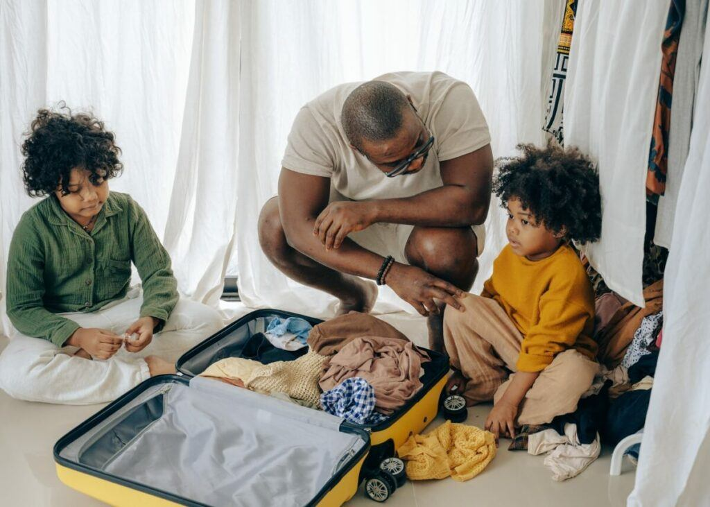 African American with his kids packing up a suitcase.