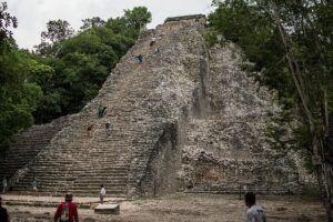 People climbing a pyramid in Coba, Mexico.
