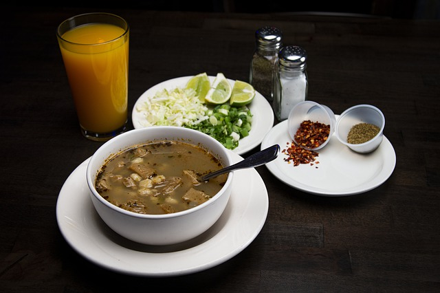 A bowl of menudo with lime, chilin and onion.