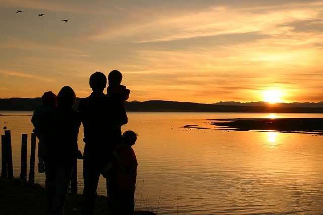 Family silhouettes looking at the sunset.
