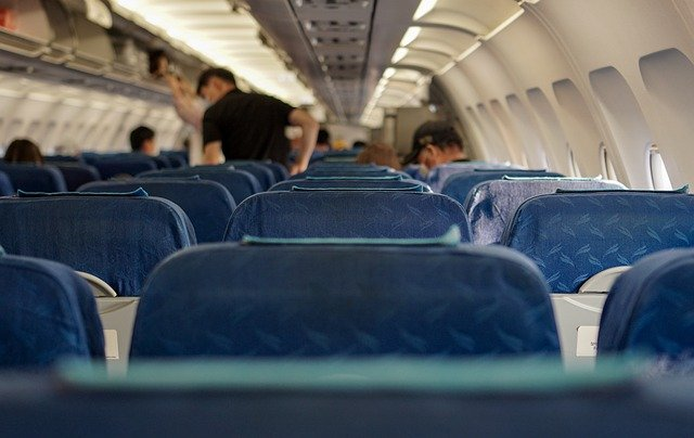 Several people inside an airplane cabin.