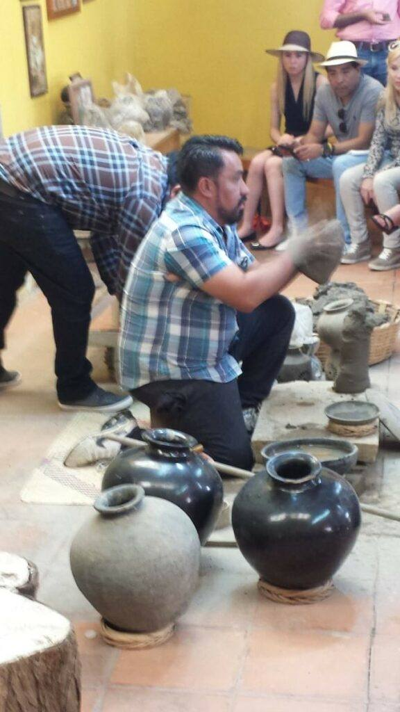 An artisan showing how to make barro negro pottery.
