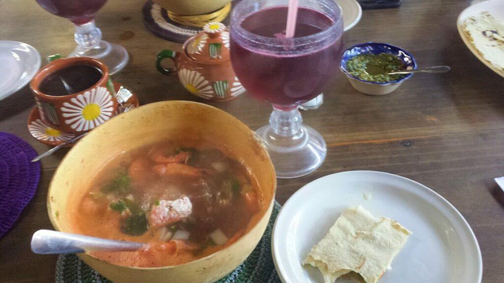 A kind of soup with fish, shrimp, and vegetables accompanied by hibiscus tea.