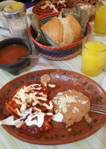 Chilaquiles rojos with cream, cheese, beans, and orange juice.