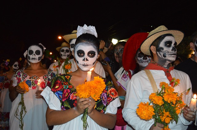 Several people dressed in traditional white clothes and holding marigolds and candles in their hands.