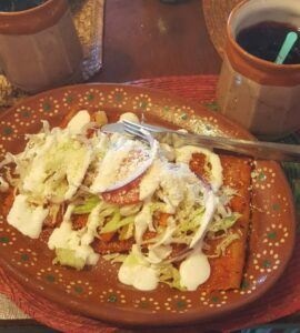Enchiladas topped with queso fresco, lettuce, and cream.