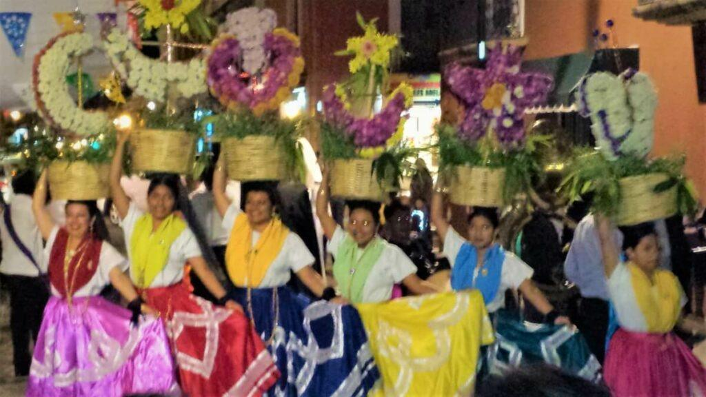 Various young women dressed in their regional costumes and holding baskets with flowers on their heads.