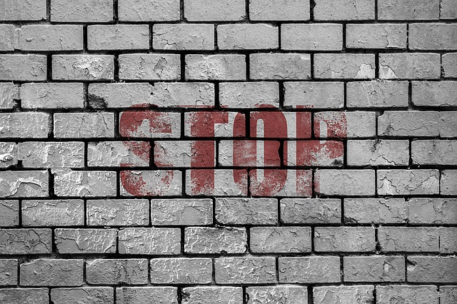 The word stop written in red letters on a gray brick wall.