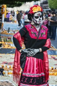 Woman wearing a black and pink dress and characterized as a catrina.