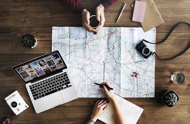 Two people planning a trip with a laptop, a notebook, and a map.