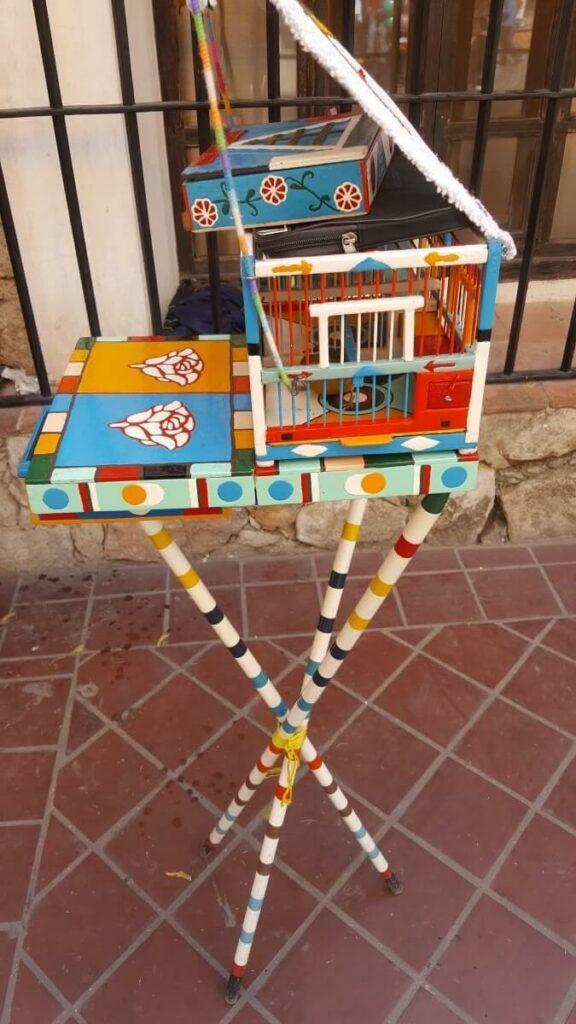 A colorful cage with a fortune bird inside.