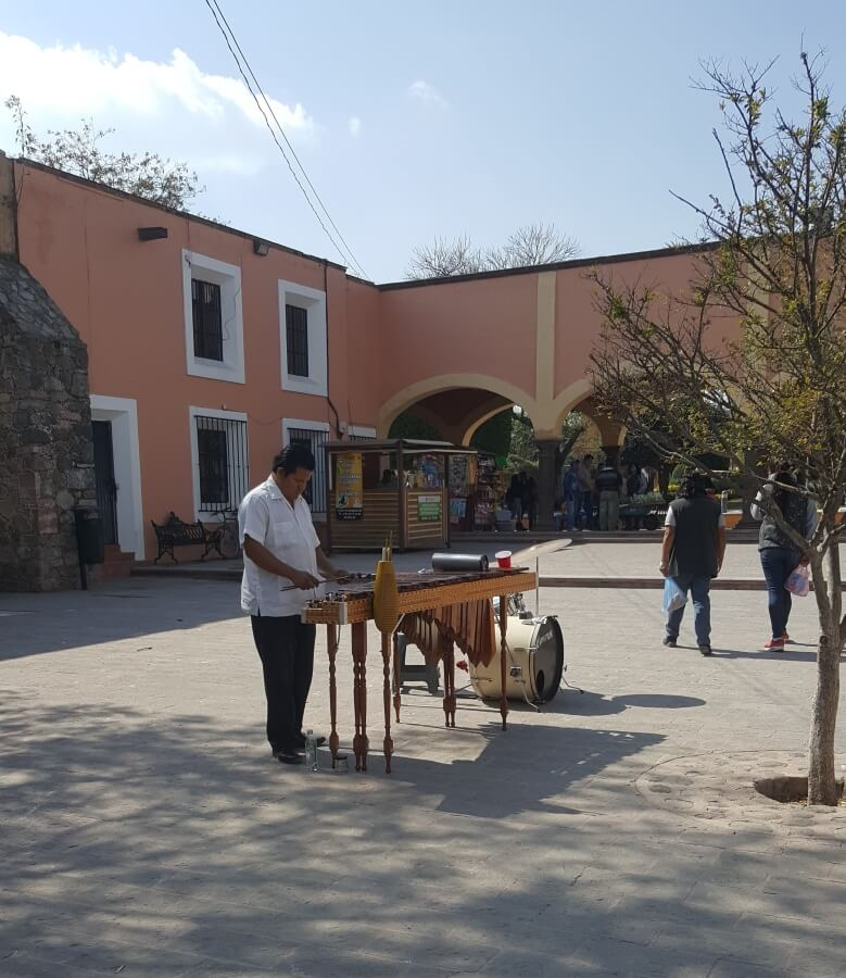 A man playing the marimba in the middle of a plaza.
