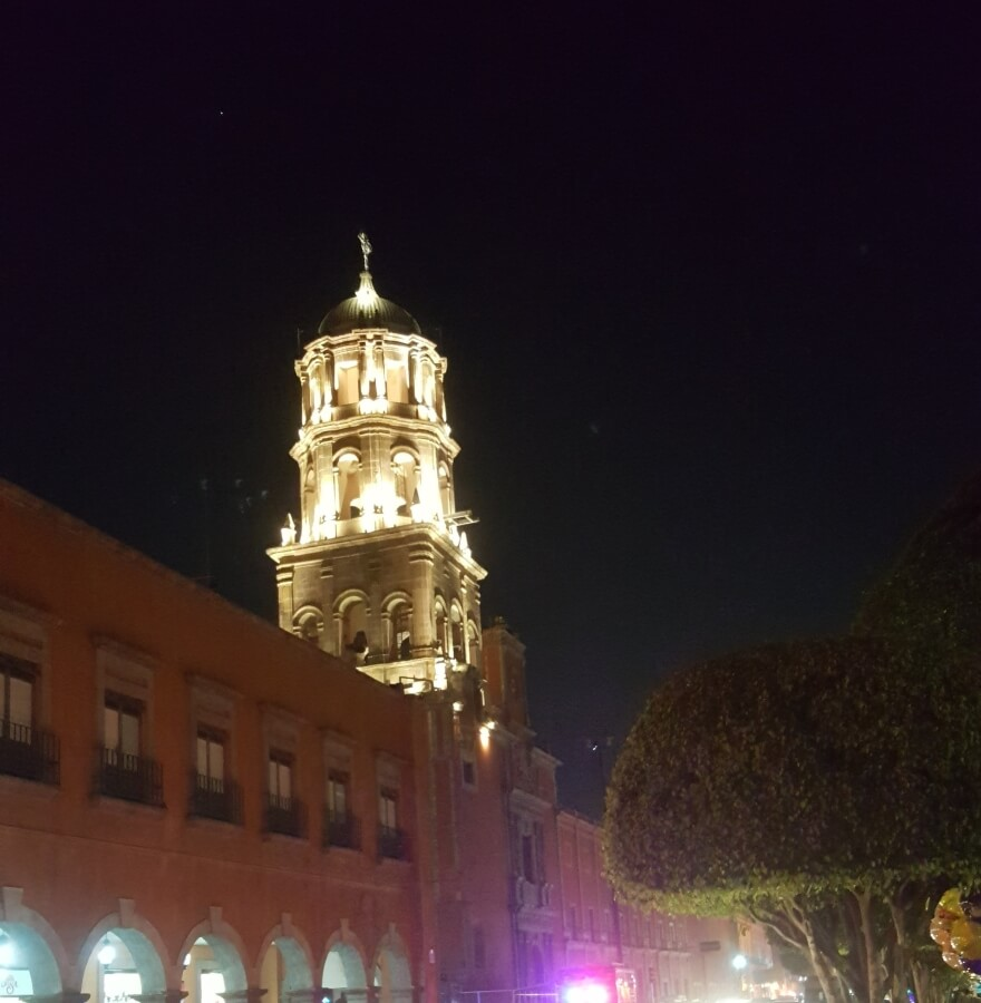 Church bell tower lit up at night.