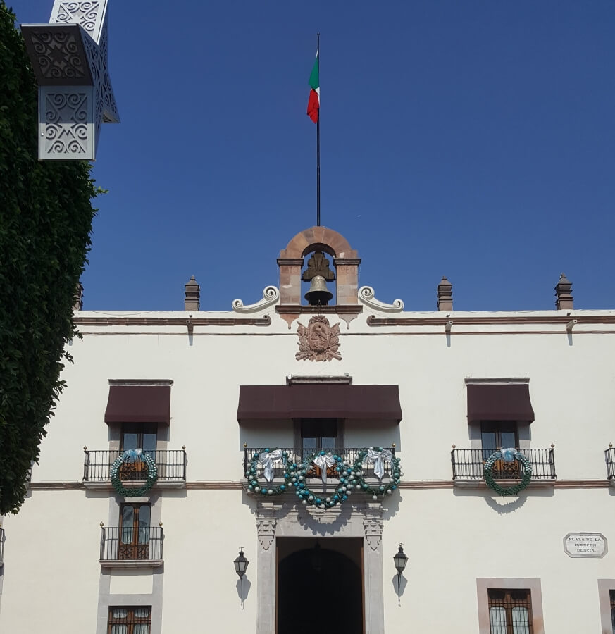 White city hall with the Mexican flag on top.